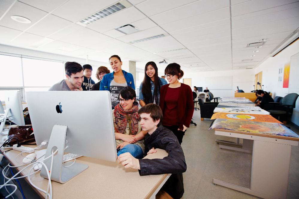 Student group working at computer monitor